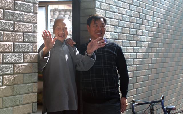 108岁老人周金莲在家门口与访客挥手告别