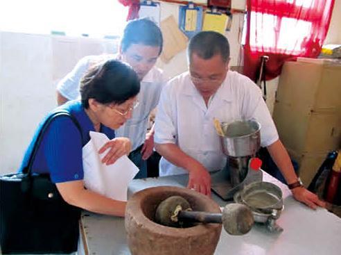 陈基海(右)展示使用的传统磨粉制膏器具