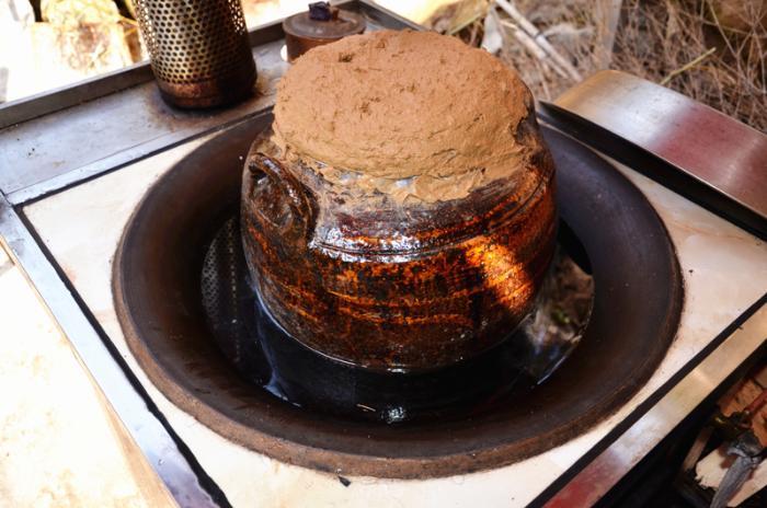 封了羊肉的酒坛置于锅中隔火蒸制